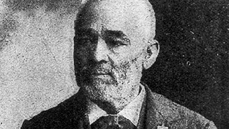 Old African American man with grey hair wearing a dark suit and tie.