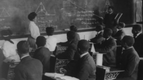 Classroom of African American men wearing dark suits facing chalkboard.