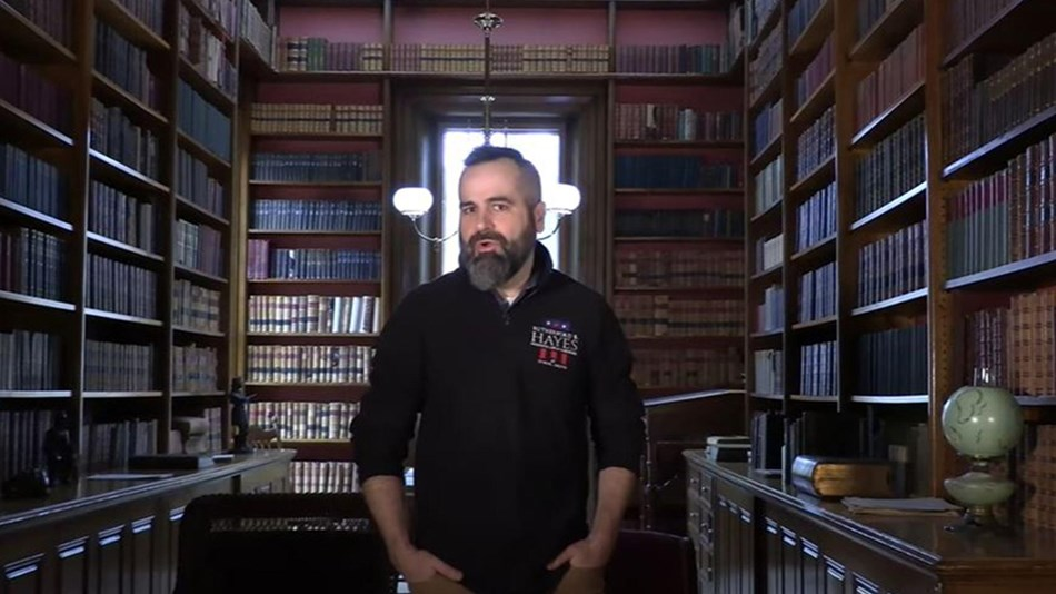 Historian Dustin McLochlin stands in a historic library.