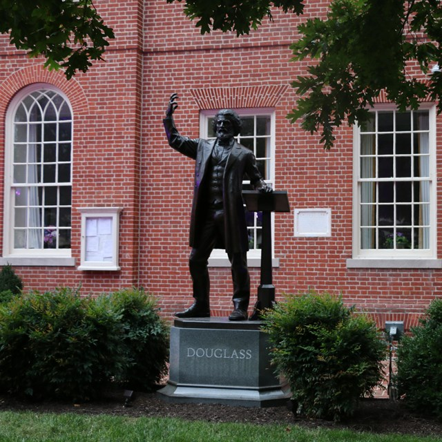 Photograph of a statue of Frederick Douglass standing in grass in front of brick buildings.