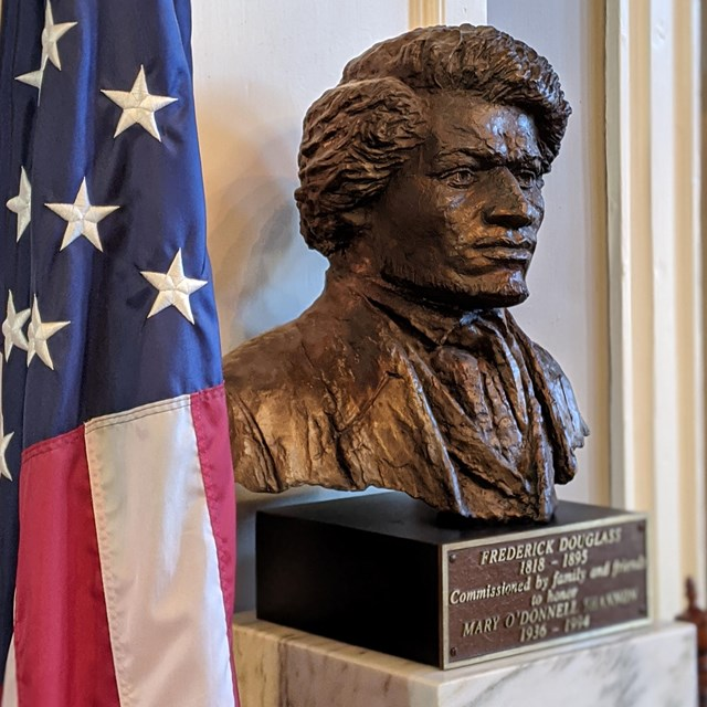 A bust of Frederick Douglass sits next to an American Flag.