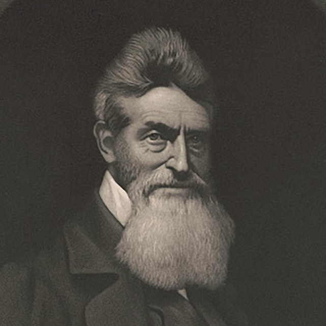 A portrait of abolitionist John Brown with short hair and a long, gray beard.