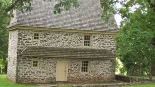 A stone house surrounded by trees where General Varnum stayed.