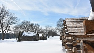Log huts in deep snow.