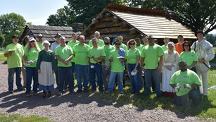 A group of people in matching company t-shirts stand in front of a hut.