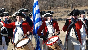 Continental Army musicians stand in line in front of a regiment outdoors in a field.