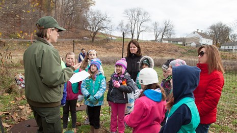 A park ranger speaks to a group of young girls in Girl Scout uniforms.