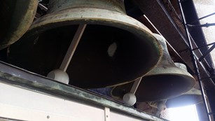 Large bells in a row in a bell tower interior.