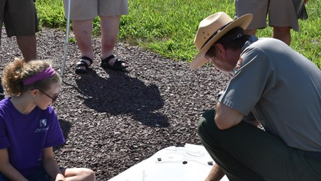 A ranger and a young visitor plan defenses using a laminated map and stones outdoors.