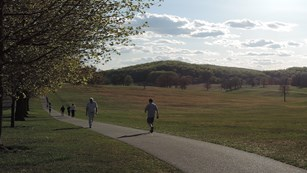 Walkers enjoy a late afternoon stroll along a paved path through a large grassy field.