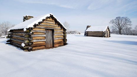 Two log huts with snow cover on  ground and hut roofs