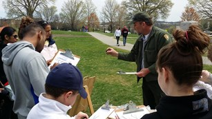 Park Ranger teaches children how to do charcoal drawings.