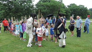 Soldiers teaching a group of children how to drill with wooden muskets.