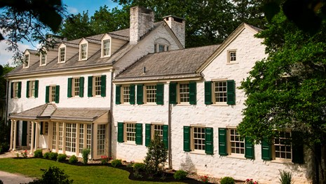 White Queen Ann style mansion with green shutters