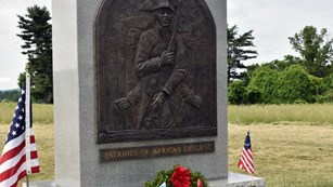A stone monument with a bronze relief of three African American Continental Soldiers.