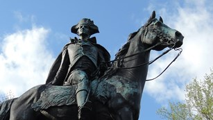 A bronze statue of a man on a horse sits atop a stone pedestal.