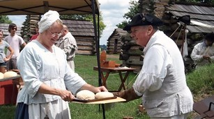 Two colonial women bring bread dough to a colonial baker at an outdoor oven.