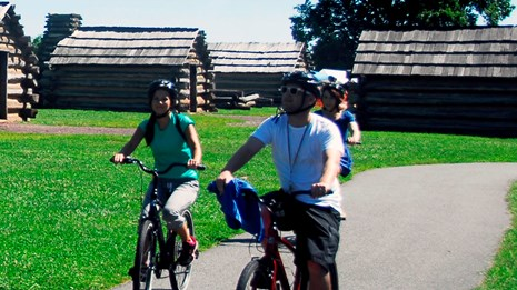 Three bicycle riders travel down a paved trail past log huts on a sunny day.