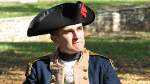 Young Continental Army officer sitting behind field desk.