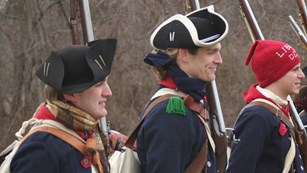Continental soldiers shoulder to shoulder hold musket against left side of body.