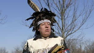 Oneida warrior wearing blue traditional garb with drum in hand.