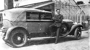 A man in a suit standing next to an automobile.