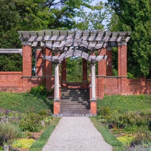 A gravel path bordered by flowers leading to a red brick and timber pergola.