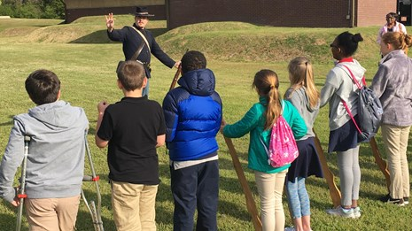 A park ranger dressed as a Union soldier teaching school children how to hold wooden muskets.