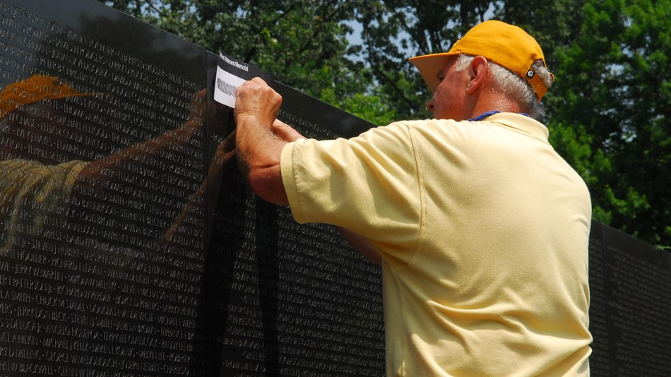 A man makes a rubbing of a name on the Vietnam Veterans Memorial