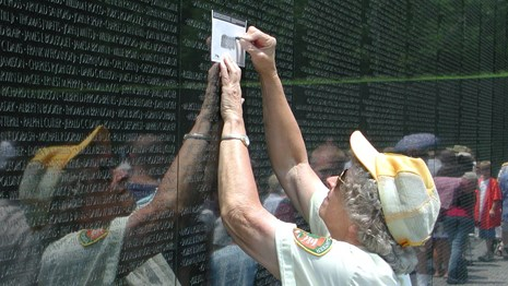 Volunteer taking a rubbing of a name on the Vietnam Veterans Memorial