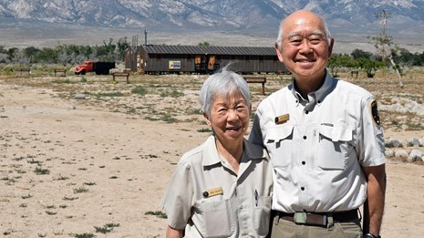 Two volunteers standing together on a desert landscape.