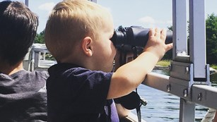 A young child sits in a tour boat and holds a pair of binoculars up to his eyes.
