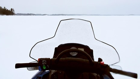 The handlebars and windshield of a snowmobile point towards a large, frozen-over scenic lake.