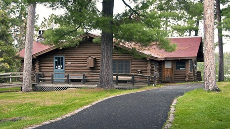The Ash River Visitor Center--a log cabin with a red roof--sits on a grassy hill surrounded by pines