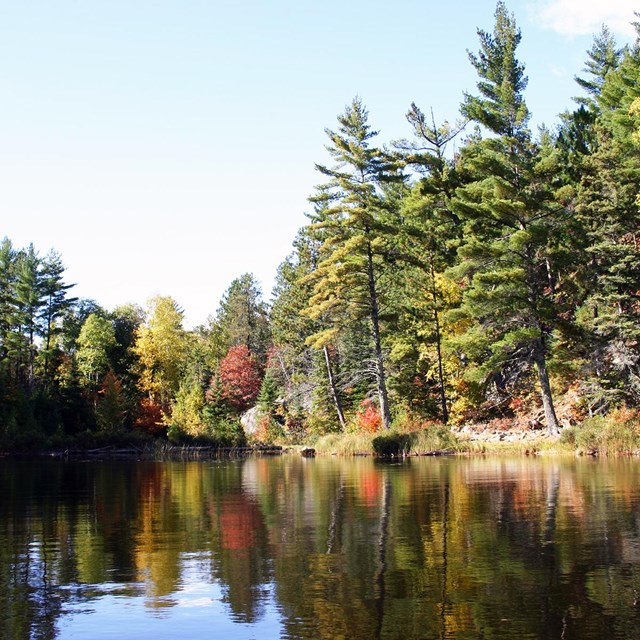 Brightly-colored trees are reflected on the water along the shore of a scenic lake.