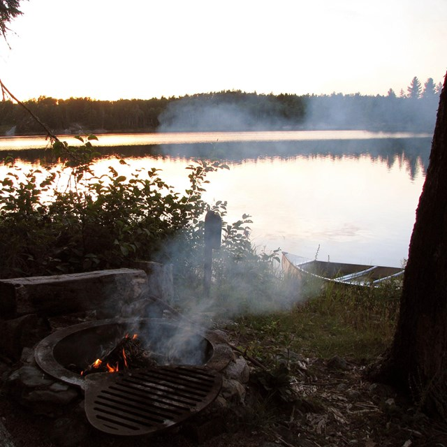 A campfire crackles in a metal grate on the shores of a scenic lake.