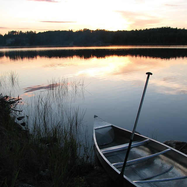 An empty canoe sits on the shore of a small, scenic lake at sunset.