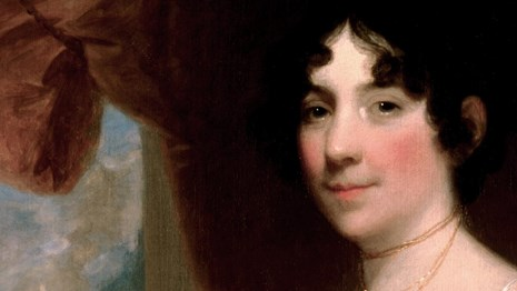 Portrait of First Lady Dolley Madison as a young woman in her 30s, surrounded by plush red velvet