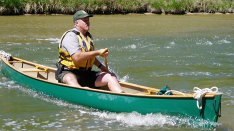 Park ranger paddling a canoe on a muddy river