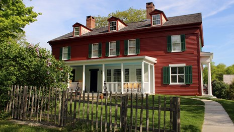 A red house with white trim and green shutters with a wooden fence in the front.
