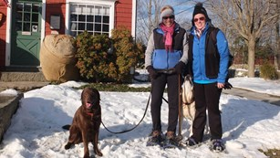 Visitors with dog standing in snow outside of Burlingham House Visitor Center