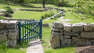 A green gate on a stone wall that leads into a green field.