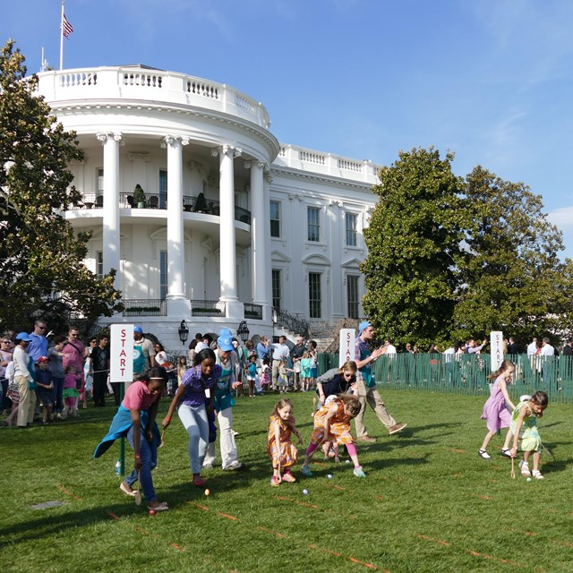 Children rolling eggs on the South Lawn
