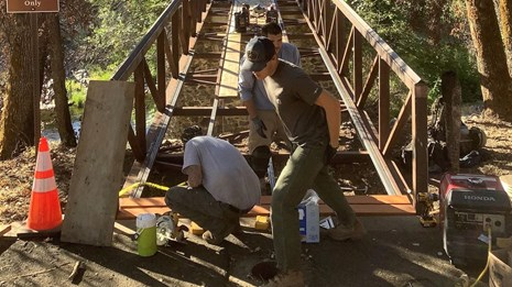 Park maintenance staff rebuilding a footbridge within Tower House Historic District