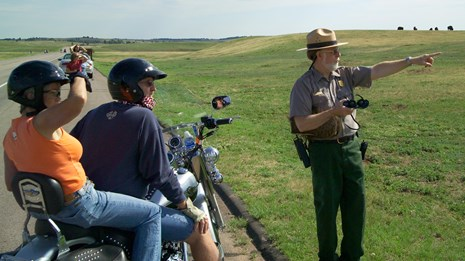 A ranger points in the distance as visitors look into the open prairie