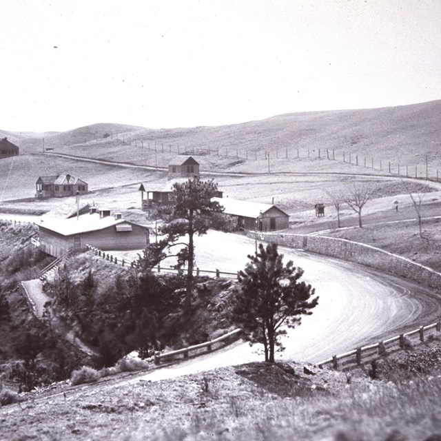 black and white photo of the parking lot, visitor center, and several park houses in 1932
