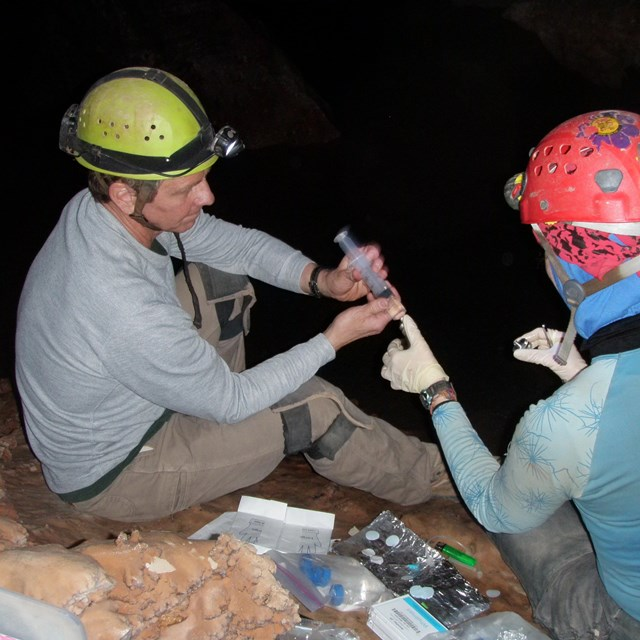 two scientists in caving gear sampling water from an underground lake