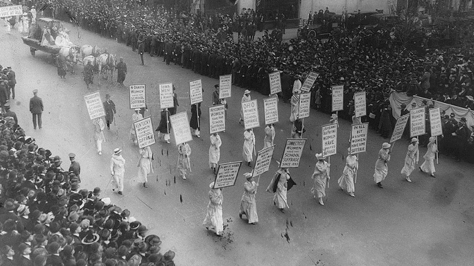 Aerial photo of women marching in parade with spectator-lined street. Library of Congress.