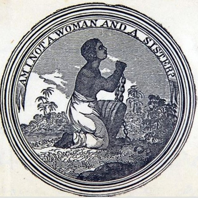Medallion of a black woman kneeling. Her hands are in bondage. Text: