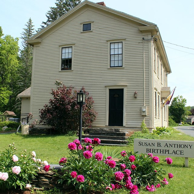 Photo of the exterior of the Susan B Anthony birthplace with flowers blooming